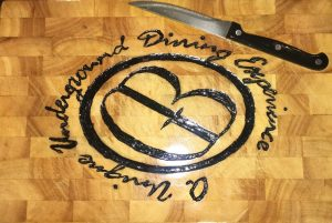 Wooden chopping board with Gary Bell logo and an embedded knife